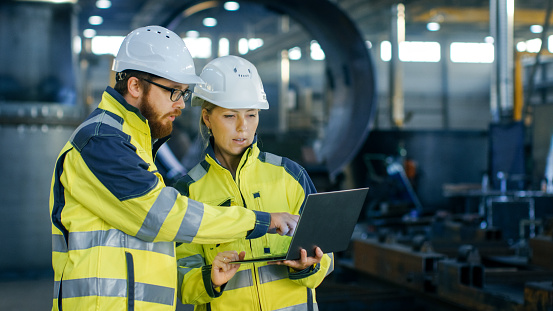Male and Female Industrial Engineers in Hard Hats Discuss New Project while Using Laptop. They Make Showing Gestures.They Work in a Heavy Industry Manufacturing Factory. 879813818