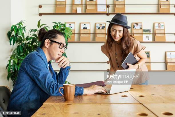 male and female japanese professional at a table in a co-working space, using laptop computer. - カジュアルウェア ストックフォトと画像