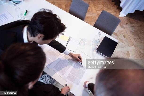 male and female lawyers reading documents while standing by office desk - legal - fotografias e filmes do acervo