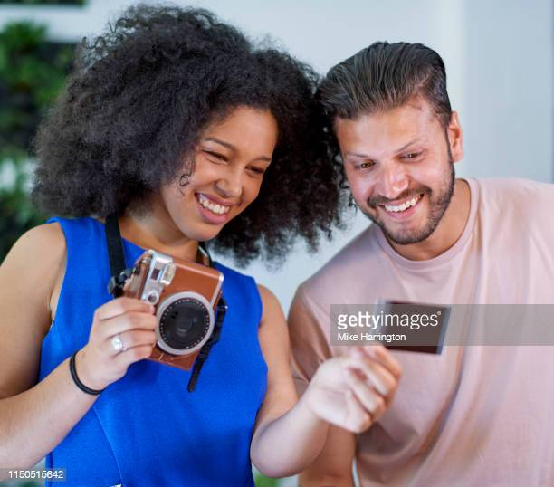 male and female looking at photo and smiling - sleeveless dress stock pictures, royalty-free photos & images