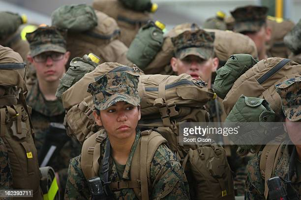 Male and female Marines rest following a 10 kilometer training march carrying a 55 pound pack during Marine Combat Training on February 22 2013 at...