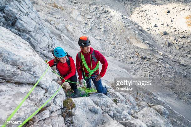 male and female mountain climber on an exposed rocky summit ridge on their way to a high alpine mountain peak - bavarian alps stock pictures, royalty-free photos & images