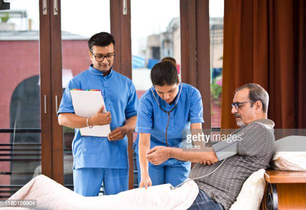 male and female nurse checking senior man's blood pressure on house call - medical insurance stock pictures, royalty-free photos & images