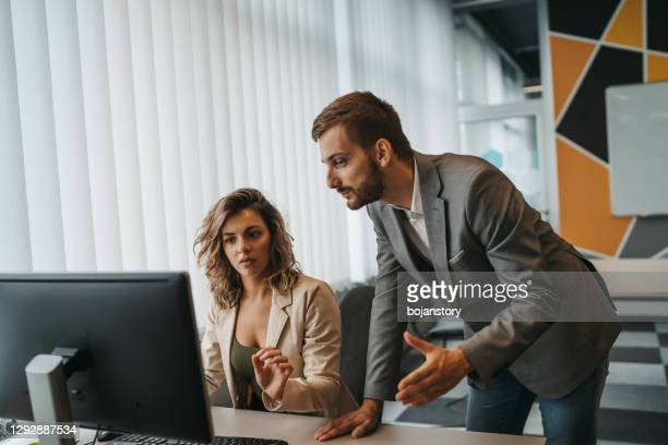 male and female office employees having argument at workplace - aggression stock pictures, royalty-free photos & images