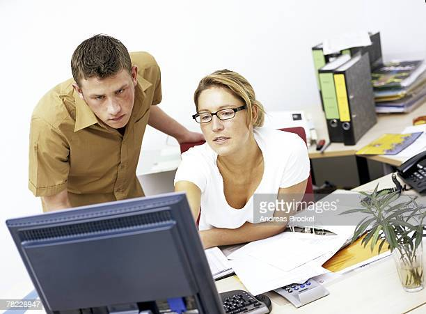 male (20-25 years) and female (25-30 years) office workers looking at flat panel monitor - 25 29 years stock pictures, royalty-free photos & images