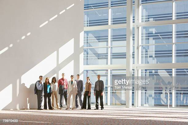 male and female office workers posing for group portrait - building atrium stock pictures, royalty-free photos & images