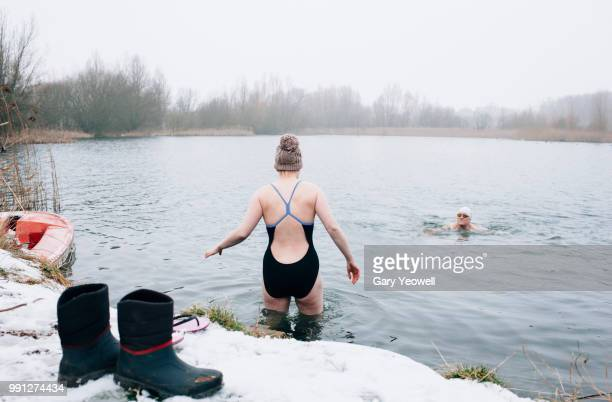 male and female open water swimmers in winter - swimming stock pictures, royalty-free photos & images