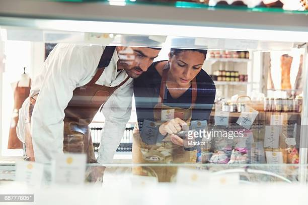 Male and female owners using smart phone while examining display cabinet in grocery store