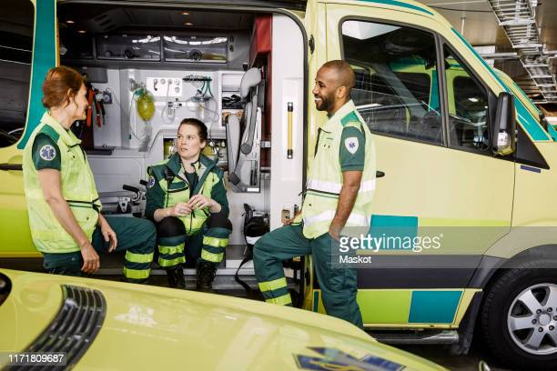 male and female paramedics talking while sitting in ambulance at parking lot - rescue worker stock pictures, royalty-free photos & images