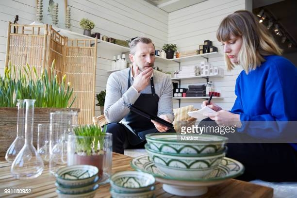 male and female partners discussing over merchandise at store - household equipment stock pictures, royalty-free photos & images