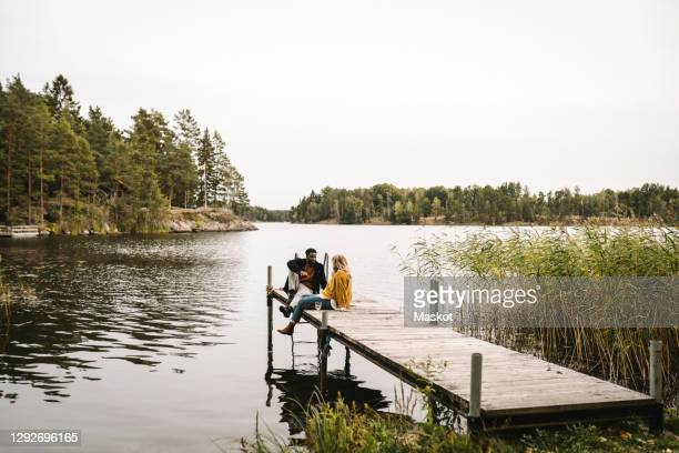 male and female partners sitting on pier over lake during social gathering - sweden stock pictures, royalty-free photos & images
