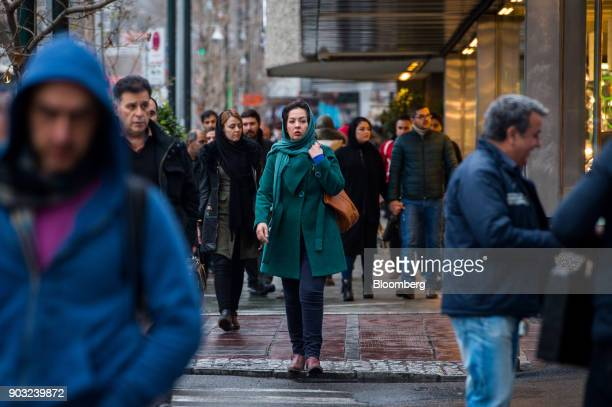 Male and female pedestrians walk along a street in Tehran Iran on Saturday Jan 6 2018 A wave of bad loans from unregulated lenders has rocked the...