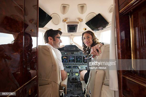 Male and female pilot looking over her shoulder in cockpit of private jet