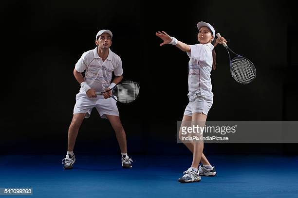 male and female players playing tennis doubles at court - doubles stock photos and pictures