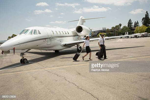 Male and female private jet pilots leaving plane at airport
