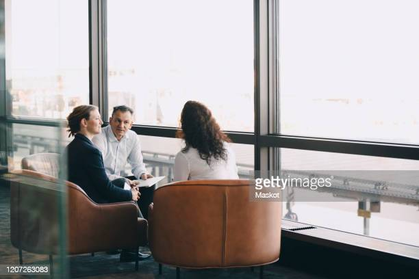 male and female professionals discussing while sitting by glass window in office corridor - 少人数 ストックフォトと画像
