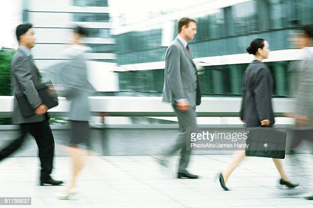 Male and female professionals walking on sidewalk, blurred motion