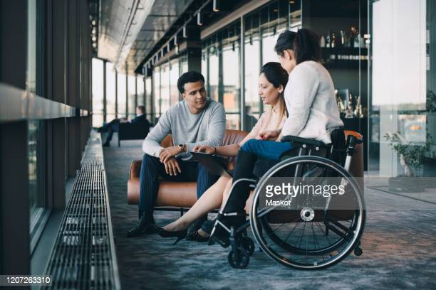 male and female professionals working on laptop with disabled entrepreneur in office corridor - disability stock pictures, royalty-free photos & images