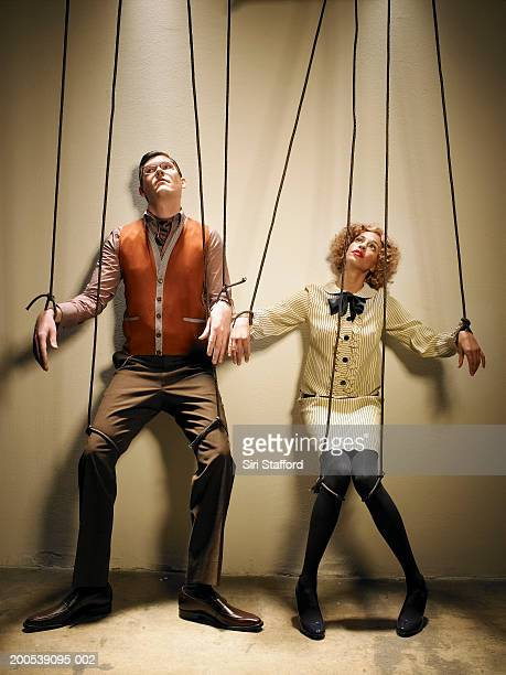 male and female puppets tied with strings - puppeteer stock photos and pictures