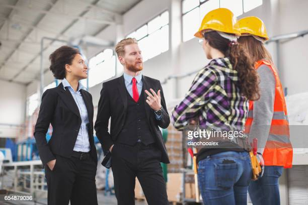 Male and female quality inspectors talking to workes in factory