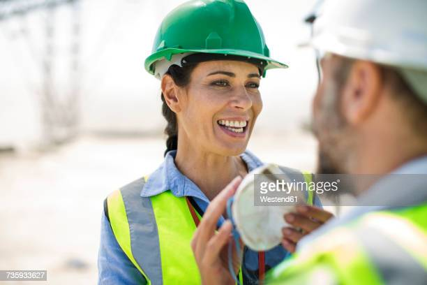 Male and female quarry workers discussing on site