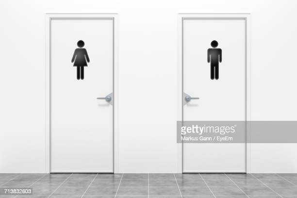male and female restroom sign on bathroom doors - deur stockfoto's en -beelden