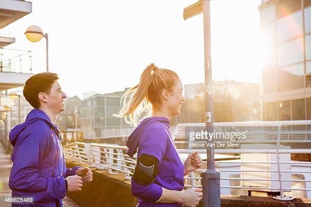 Male and female runner running in city.