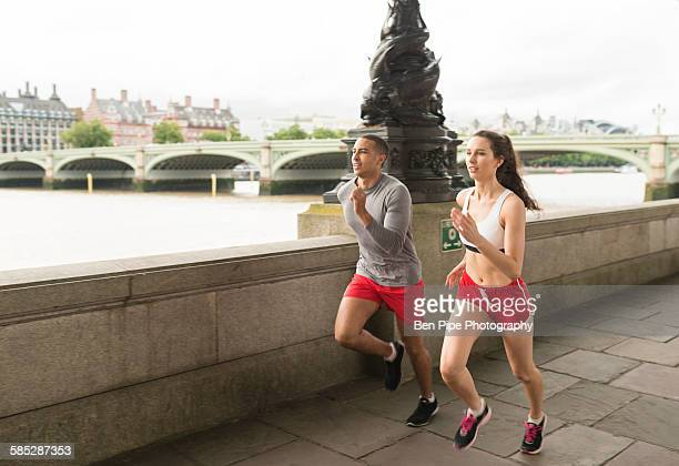 Male and female runners running on Southbank, London, UK