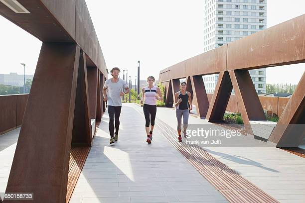 Male and female runners running on urban footbridge