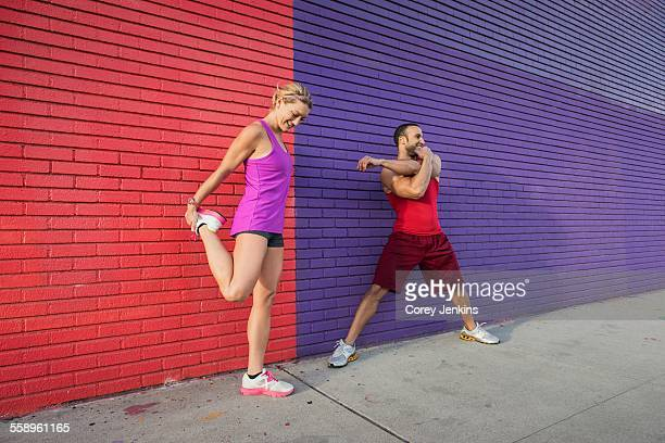 Male and female runners warming up on sidewalk