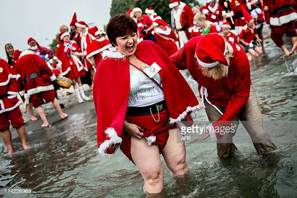 Male and female Santas from all over the world take a dip in Oeresund Bellevue Beach north of Copenhagen on July 22 2013 during the annual Santa...