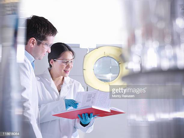 Male and female scientists discussing notes in laboratory