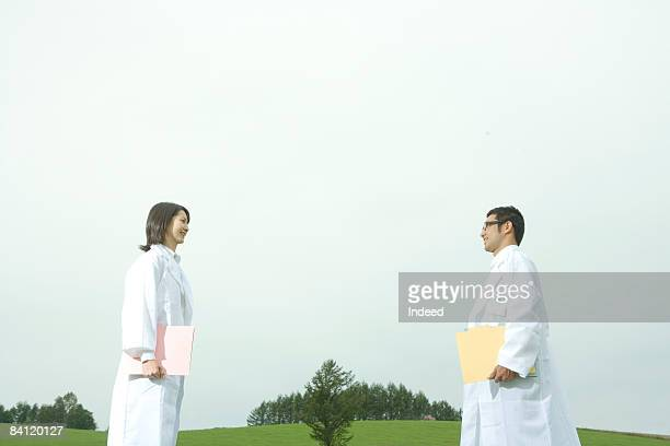 Male and female scientists smiling face to face
