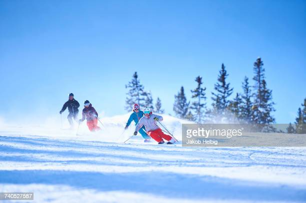 male and female skiers skiing down snow covered ski slope, aspen, colorado, usa - aspen colorado stock photos and pictures