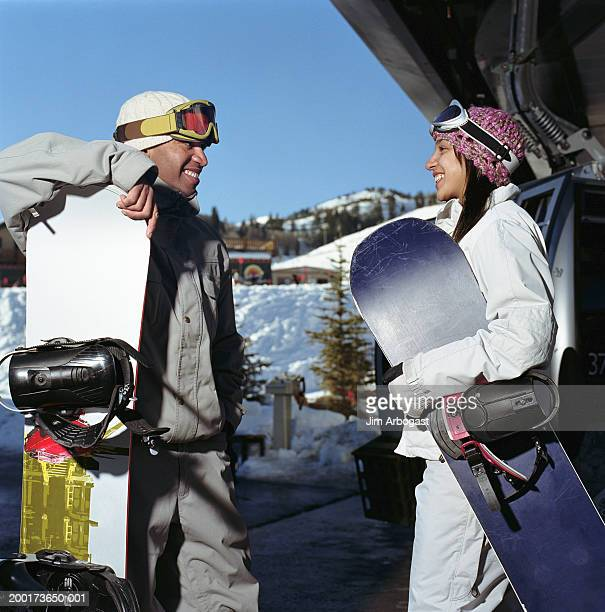male and female snowboarders smiling at one another, side view - travel14 stock pictures, royalty-free photos & images