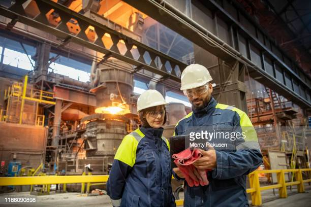 male and female steelworkers using digital tablet during steel pour in steelworks - safety stock pictures, royalty-free photos & images