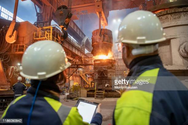 male and female steelworkers using digital tablet during steel pour in steelworks - monty rakusen stock pictures, royalty-free photos & images