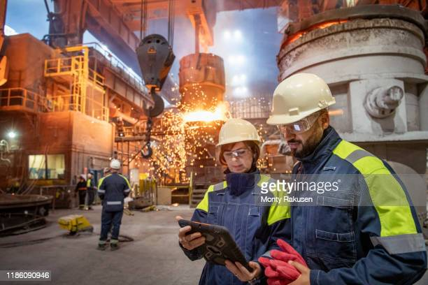 male and female steelworkers using digital tablet during steel pour in steelworks - built structure stock pictures, royalty-free photos & images