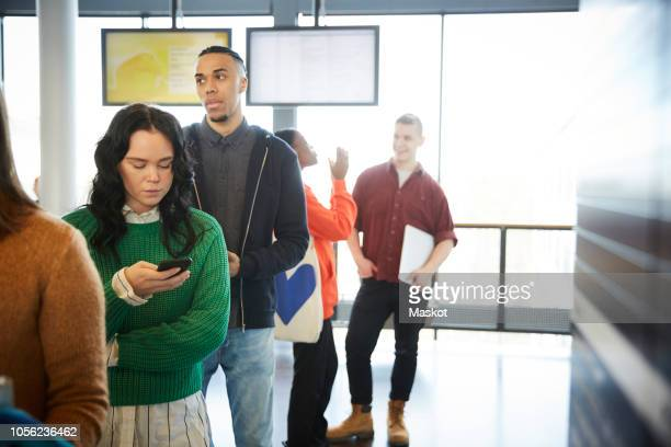 male and female students standing in queue at university - lining up stock pictures, royalty-free photos & images