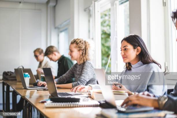 male and female students using laptops in classroom - college student stock pictures, royalty-free photos & images