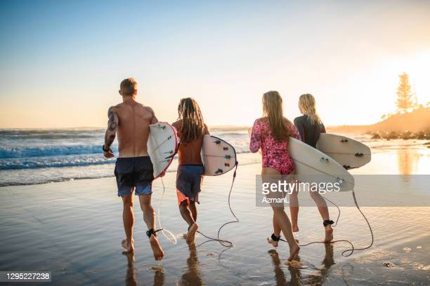 male and female surfing friends at burleigh heads - coral sea stock pictures, royalty-free photos & images