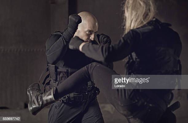 male and female swat team members fighting in urban setting - martial arts stock pictures, royalty-free photos & images