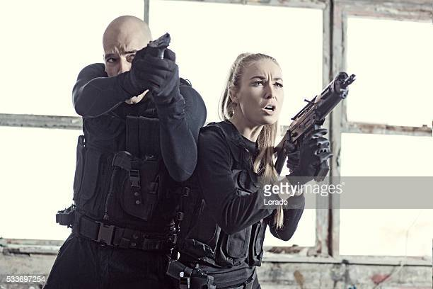Male and Female swat team members working in urban setting and Female swat team members in urban setting