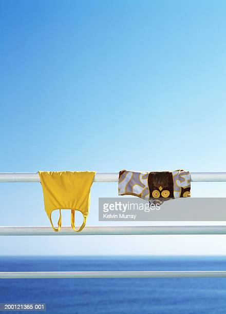 Male and female swimming costumes hanging on railing, close-up