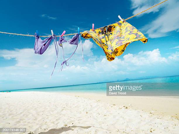 Male and female swimwear hanging on line at beach