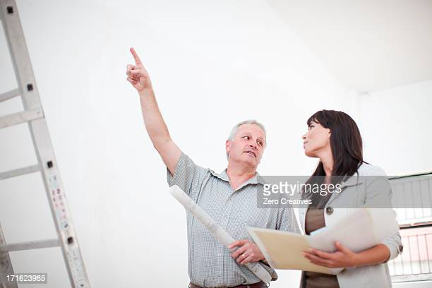 Male and female  talking and pointing upwards holding  blueprints next to ladders