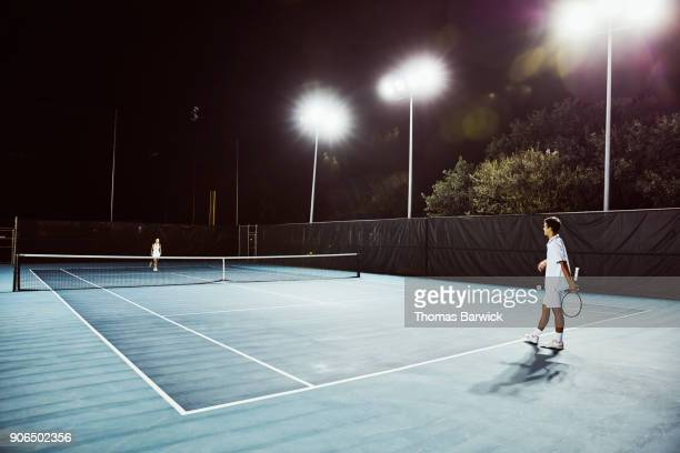 Male and female teenage tennis teammates in discussion while practicing on outdoor court at night