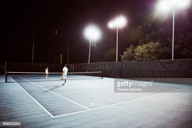 Male and female teenage tennis teammates practicing on outdoor court at night