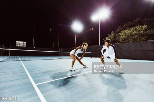 Male and female tennis teammates stretching on court at night before practice