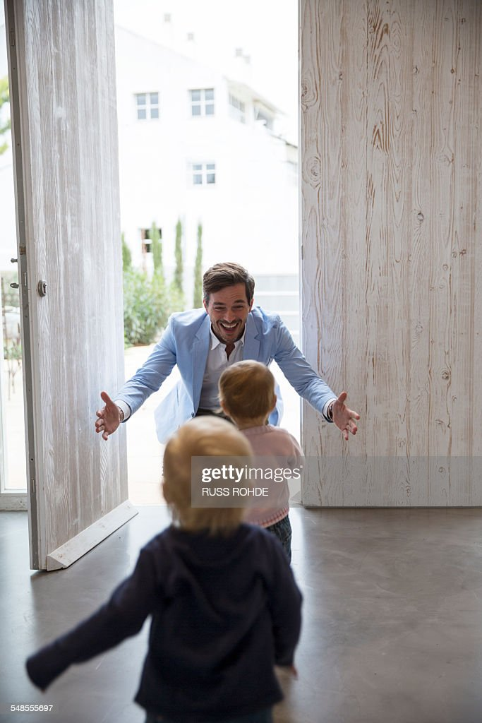 Male and female toddler twins running to fathers arms at front door : Stock Photo